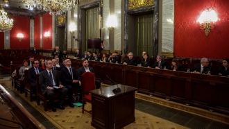 Former Catalan separatist leaders sit on the front bench at the beginning of their trial.