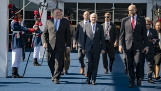 Secretary of State Mike Pompeo walks with adviser Michael McKinley
