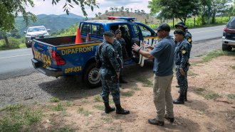 A U.S. DHS advisor instructs Guatemalan border police at a temporary checkpoint on August 27, 2019