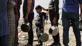 Syrian refugees wait for water at a refugee camp in Iraq