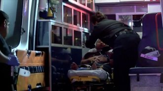 A man is treated in the back of an ambulance after a shooting in Fresno, California.