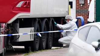 Forensic officers investigate a truck in which 39 bodies were discovered in the trailer