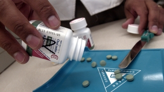 A pharmacist pours out a bottle of Oxycontin