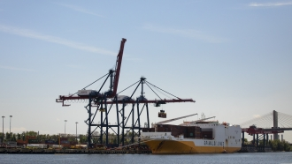 Cranes load shipping containers onto a cargo ship in Staten Island.