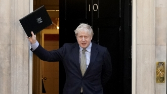 British Prime Minister Boris Johnson waves to the public outside of his residence on Downing Street