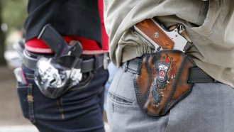 Two people with holstered handguns