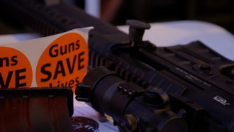 "A ""Guns Save Lives"" sticker and a rifle during VCDL's Lobby Day."