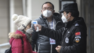 Authorities check a woman's temperature in Wuhan, China