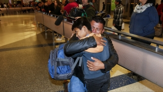 David Xol-Cholom hugs his son Byron at Los Angeles International Airport as they reunite after being separated