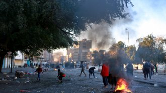 Protesters set fire to close a street during clashes between security forces and anti-government protesters.