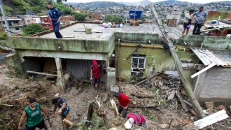 Locals work to clean up mud and debris around houses destroyed by a landslide in Brazil