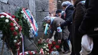 Holocaust survivors lay flowers at the Auschwitz-Birkenau concentration camp