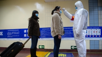 A health worker checks a person's temperature