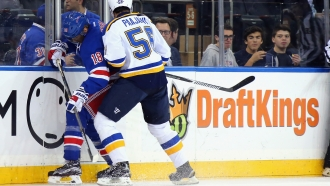 The New York Rangers and St. Louis Blues skate in front of a dasher board advertising the betting website DraftKings