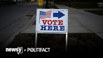 A voting sign sits outside.