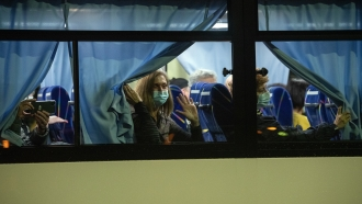 Americans look out from the bus taking them from the quarantined Diamond Prince Cruise Ship in Yokohama, Japan.