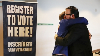 Two men with felony records hug after turning in their voter registration forms in Florida