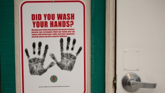 A sign reminding firefighters to wash their hands near a dormitory unit to be used for quarantine of travelers