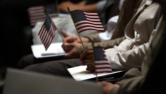 People holding American flags during naturalization ceremony