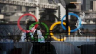 Olympic rings and people wearing protective masks