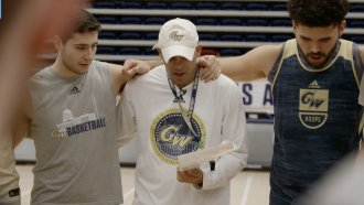 George Washington University basketball coach Jamion Christian stands with players