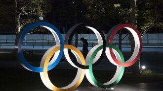 Person stands behind Olympics rings logo.