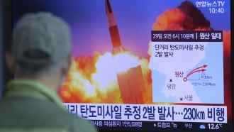 A man watches a TV screen showing a file image of North Korea's missile launch during a news program
