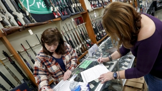 Andrea Schry, right, fills out the buyer part of legal forms to buy a handgun.