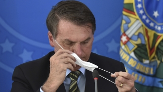 Brazil's President Jair Bolsonaro puts on a mask during a coronavirus press conference on March 18.