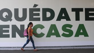 "A woman walks past a sign that reads in Spanish ""Stay home"" in Mexico City, Tuesday, March 31, 2020."