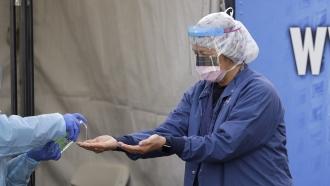A registered nurse, has hand sanitizer applied on her hands after removing her gloves.