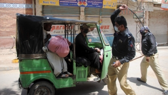 Police officers in Pakistan approach a rickshaw driver defying the nationwide lockdown to curb the spread of the coronavirus
