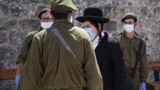 Masked Israeli soldiers and civilian in Jewish quarter of Jerusalem's Old City on Tuesday.