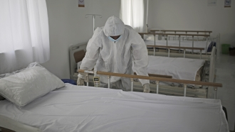 A medical staff member adjusts the sheets on a bed at a hospital in Yemen