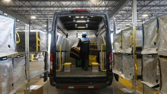 An Amazon delivery driver moves stowed containers into his truck