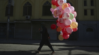 A man walks with colored balloons for sale during the first day of Eid al-Fitr