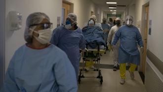 Brazilian medical workers move coronavirus patient