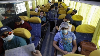 Overseas Filipino workers, who got quarantined as they arrived in the country weeks ago, wait inside a bus.