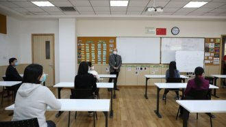 Desks are spaced out while people at YK Pao School in Shanhai are required to wear masks