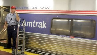 A skycap stands next to an Amtrak train.