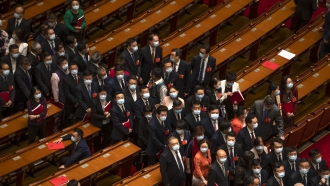 Delegates wait to leave after the closing session of China's National People's Congress
