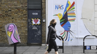 A person walks past a mural painted on the side of a pharmacy in Stoke Newington area of London