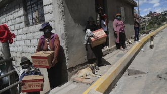 Residents near Andean city of Quito, Ecuador, gather government-distributed food boxes.