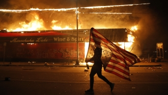 Minnesota protester carries a U.S. flag upside down