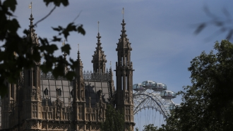 The London Eye stands behind the roof of Parliament in London, Tuesday, June 2, 2020.