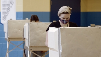 Voters cast ballots while wearing masks.