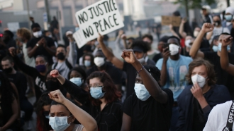 Protesters in Paris hold posters during a demonstration.