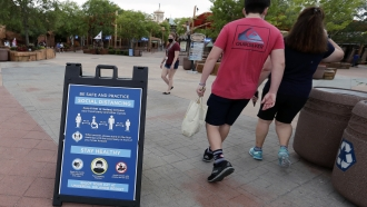 signs about social distancing and other protocols are seen about Universal Studios theme park as guests walk by