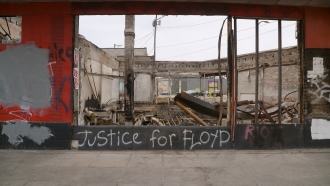 """""""Justice for Floyd"""" painted on burned building"""
