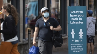 Man passes sign promoting social distancing, two days before UK city of Leicester went into lockdown amid a COVID-19 spike.